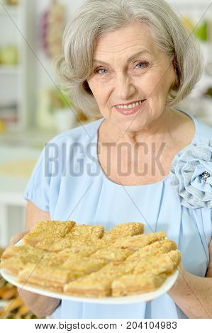 senior woman holding plate with delicious cookies