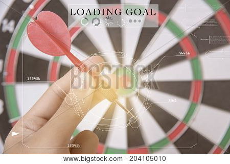 hand holhing red arrow target center of dartboard. concept technology business goal to marketing success.