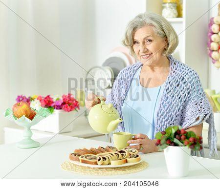 Portrait of a senior woman pouring tea at kitchen
