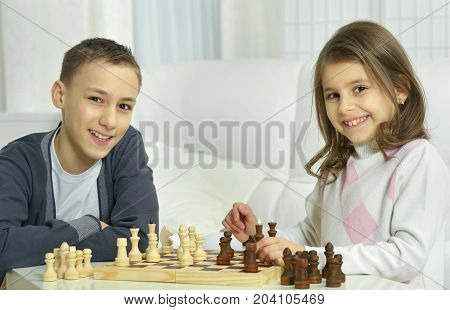 Portrait of a brother and sister playing chess together
