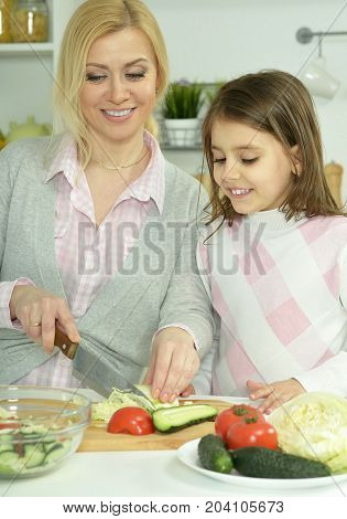 smiling mother and daughter cooking together at kitchen