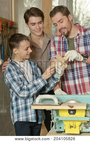 Father and sons working together in workshop