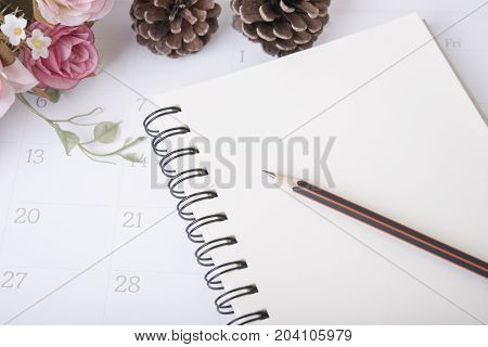 closeup pencil on notebook diary with calendar and rose flower. organization management remind concept.