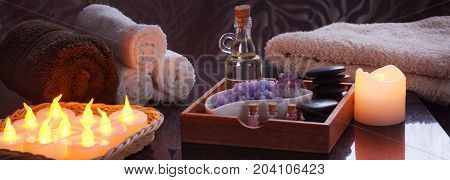 Set for spa treatments with electric burning candles and terry towels. In a wooden box oil and stones for massage, purple salt and amethyst, a set of multi-colored salt in jars