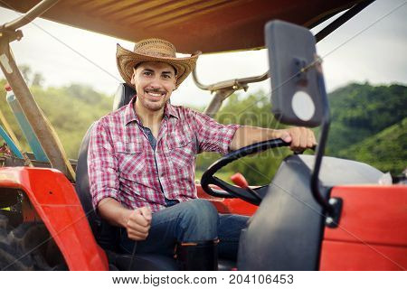 Farmer driving tractor in the fields during harvest in countryside. worker sitting on his tractor smiling.