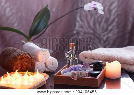 Set for spa treatments with electric burning candles and terry towels. In a wooden box, oil and stones for massage, purple salt and amethyst, an orchid in the background.