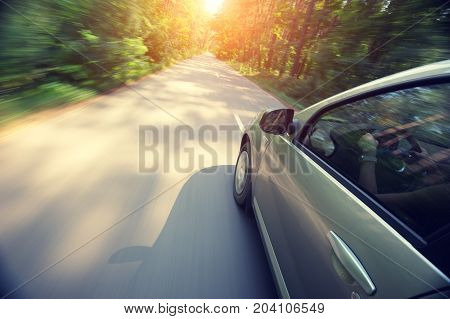The car moves at fast speed at sunrise in the forest