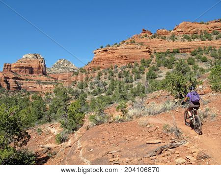 Woman mountain biking in the red rocks, Sedona, Arizona, USA