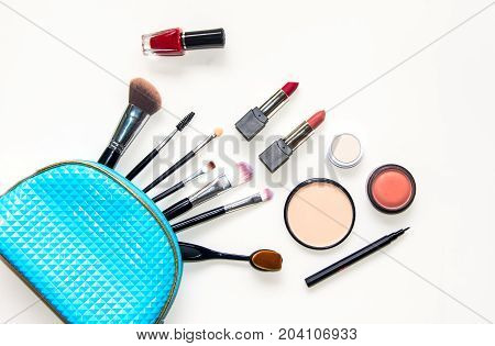 Cosmetics and fashion background with make up artist objects: lipstick eye shadows mascara eyeliner concealer nail polish with blue bag cosmetic. Lifestyle Concept