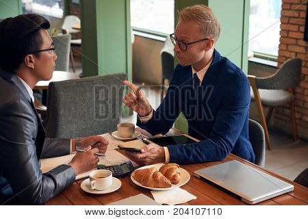 Businessman telling his idea to coworker at the meeting in cafe