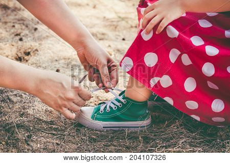 Friendly Family. Loving Mother Helping Her Little Daughter To Tie Shoelaces.