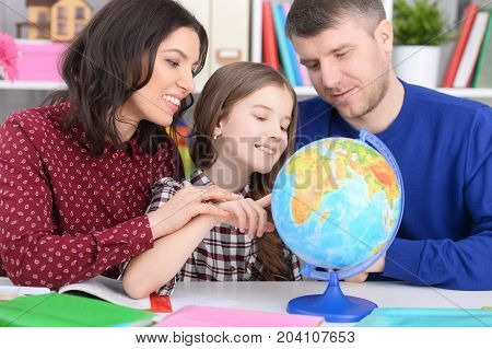 parents and daughter looking at world globe in room