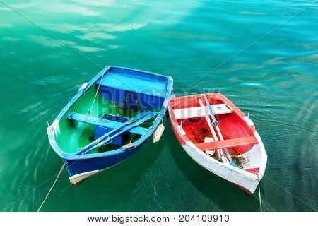 A photo of vibrant small fishermen's boats in San Vicente de la Barquera, in Cantabria, Spain, docked in a marina, with a place for text