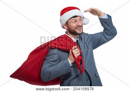 Portrait of happy santa claus with red full bag with presents, holding hand over eyes, looking at distance away. Smiling santa wearing in gray suite and red cap.  Concept of new year and christmas.