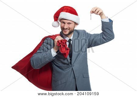 Portrait of happy smiling man in suite and red cap, like santa holding bag with presents over shoulder and showing key with arm up. Young santa clause giving in present house or car for xmas.