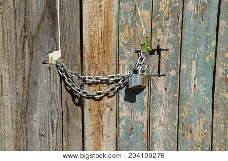 Old wooden door closed with chain and padlock