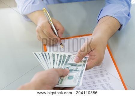 Business And Finance Concept, Hand Of A Businessman Giving Money To His Partner When Sign Contract