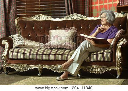 Beautiful senior woman sitting on old retro couch and reading book