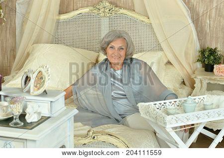 Beautiful senior woman having breakfast in bed