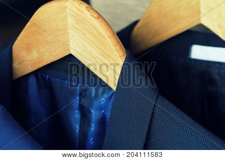 Row of men's suits hanging on rack for sale .