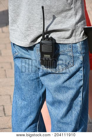 Man stands with a walkie-talkie in his pocket