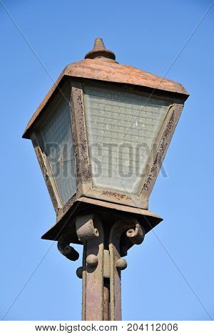 Old rusty street light against blue sky