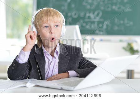 Boy in school uniform with headphones and laptop
