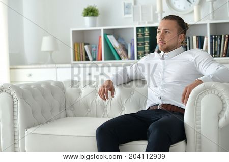 handsome young man posing on white couch
