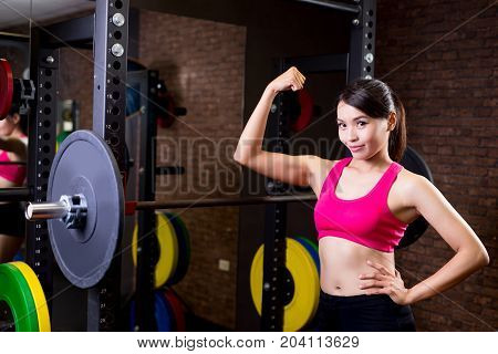 woman with barbell and show strong arm in the gym