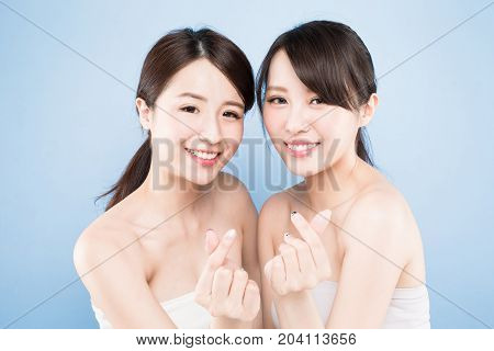 two beauty woman show heart gesture with healthy skin care on the blue background