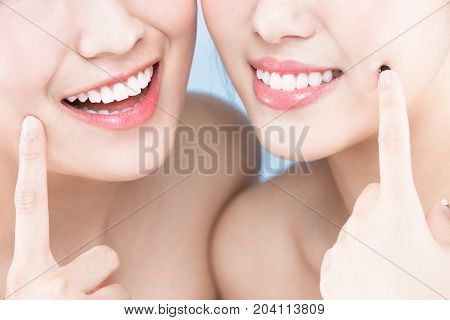 two beauty woman with healthy teeth on the blue background