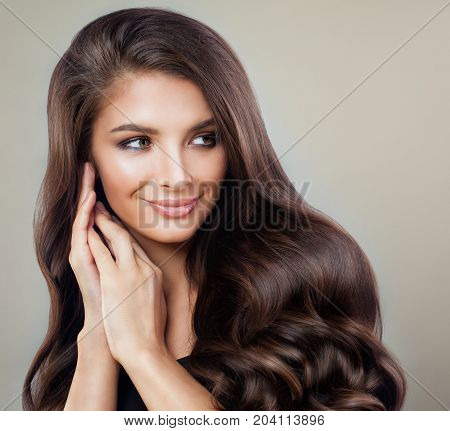 Brunette Woman with Perfect Hairstyle and Makeup. Beautiful Model with Long Healthy Hair Smiling