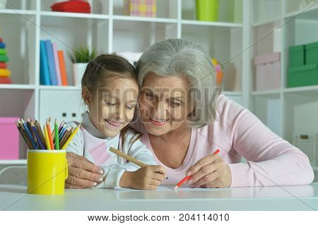 happy Grandmother with granddaughter drawing together in room