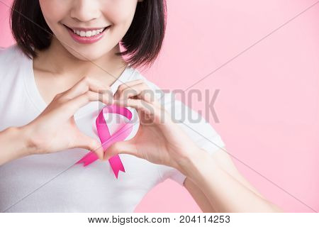 woman show heart to you with chest health concept on the pink background