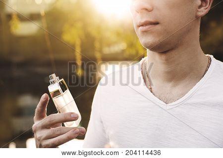 Male perfume. man holding perfume at sunset