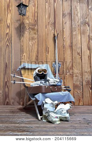 suitcase and material of winter sport on a deckchair on wooden terrace