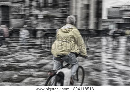 Blurred rear view of speedy cyclist on urban square after rain.