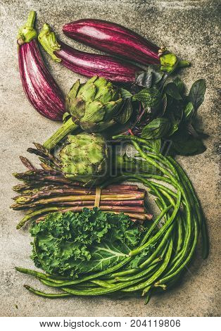 Flat-lay veriety of green and purple vegetables over concrete background, top view. Local seasonal produce for healthy cooking. Eggplans, green beans, kale, asparagus, artichoke, basil. Clean eating