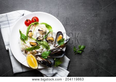 Risotto with seafood. White rice with mussels. Top view on black slate table.