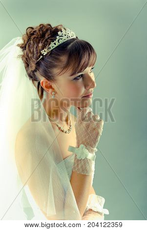 Beauty young bride dressed in elegance white wedding dress gray studio background