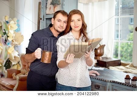 Couple reading a book of recipes to cook some dishes. Happy together, cooking concept.