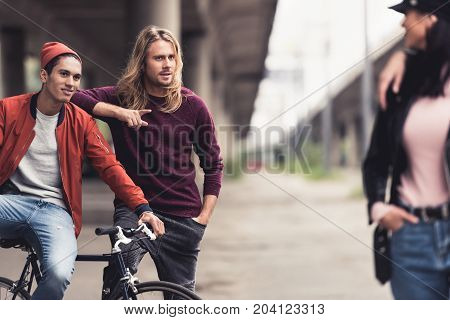 young handsome men flirting with stylish woman passing by