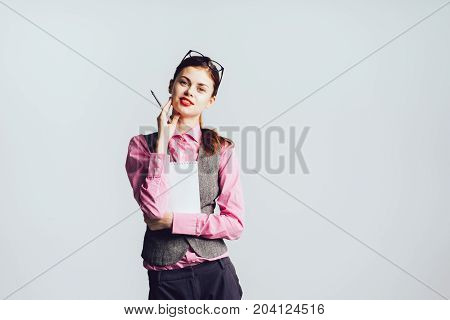 Beautiful girl with a tablet notepad for paper and pen confidently looks at the camera