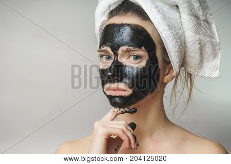 Sad woman applied skin care black mack to face.moisturizer