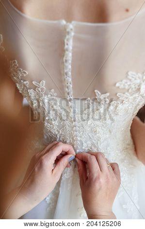 bridesmaid helps dress the bride to white wedding dress.