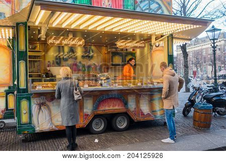 The Hague the Netherlands - 26 November 2016: people buying fresh oliebollen at a street vendor in The Hague