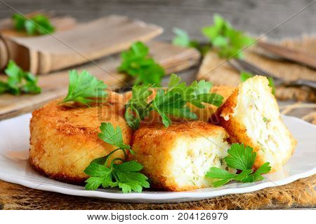 Stuffed vegetable cutlets on a serving plate. Cutlets cooked from cauliflower and potatoes and stuffed with hard boiled sliced eggs. Rustic style. Closeup