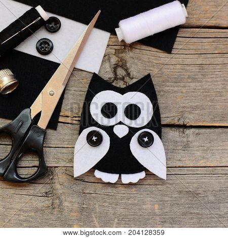 Stuffed felt owl toy, black and white felt sheets, scissors, threads, buttons on an vintage wooden background. How to teach a child to sew by hand at home. Adorable felt crafts for kids. Top view