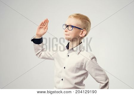 Caucasian schoolboy with his hand raised ready to answer a question. Boy pretending to be a robot