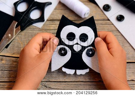 Child made a felt owl toy. Child holds a felt owl crafts in his hands. Basic sewing skills to create a felt and fabric owl ornament. Teaching a child to sew. Craft supplies on a wooden table. Closeup